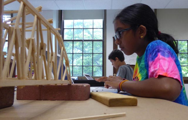 Girl at computer with truss bridge